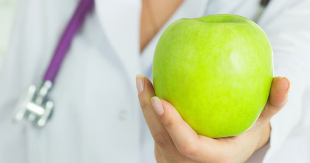 a doctor offering a green apple